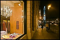 Luxury storefront and Place Vendome column by night. Paris, France