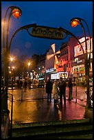 Art deco subway entrance and Moulin Rouge by night. Paris, France