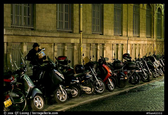 Scooters parked on a sidewalk at night. Paris, France (color)