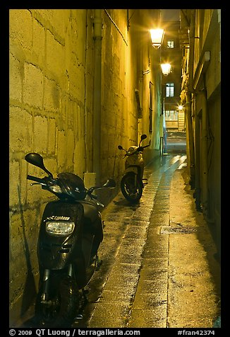 Motorcycles parked in narrow alley at night. Quartier Latin, Paris, France (color)