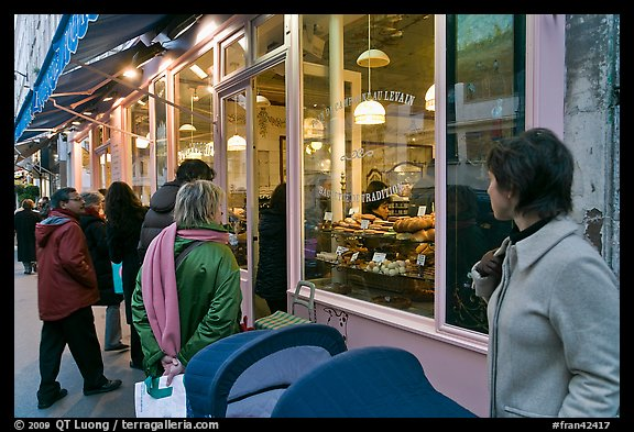 Customers wait in line in front of a popular bakery. Paris, France (color)