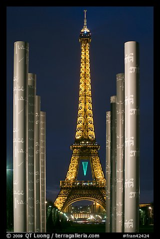 Columns of memorial to peace end Eiffel Tower by night. Paris, France