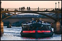 Tour boat below Pont des Arts at sunset. Paris, France