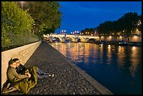 Couple sitting on quay on banks of the Seine River. Paris, France