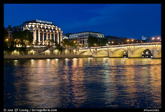 Pont Neuf and Samaritaine reflected in Seine River at night. Paris, France