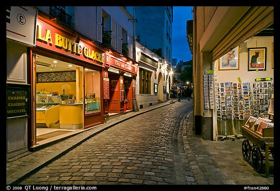Narrow cobblestone street and businesses at night, Montmartre. Paris, France (color)