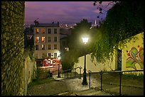 Hillside stairs of butte Montmartre and street lights at sunset. Paris, France