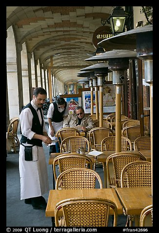 Waiters and customer, place des Vosges arcades. Paris, France (color)