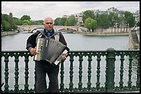 Street musician playing accordeon on River Seine bridge. Paris, France