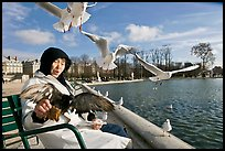 Elderly woman and seagulls, Tuileries garden. Paris, France