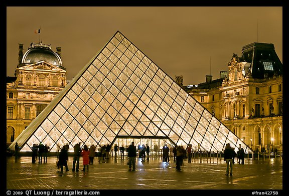 People standing in front of Louvre Pyramid by night. Paris, France (color)