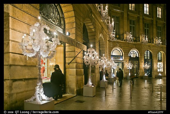 Looking at the storefronts of luxury stores at night, Place Vendome. Paris, France (color)