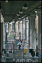 Youngsters skateboarding below metro bridge. Paris, France (color)