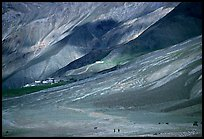 Barren hills with figures walking towards Karsha monastery, Zanskar, Jammu and Kashmir. India (color)