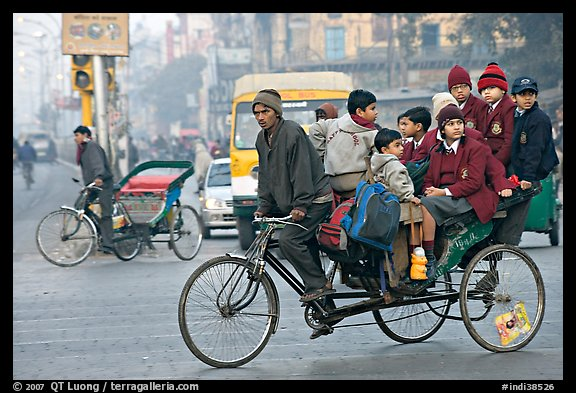 Cycle-rickshaw with a load of ten schoolchildren. New Delhi, India (color)