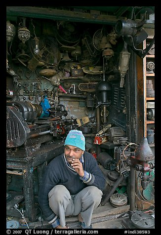 Man sitting in front of machine parts shop, Old Delhi. New Delhi, India (color)