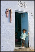 Young boy in doorway of house painted light blue. Jodhpur, Rajasthan, India (color)