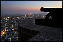 Cannon on top of Mehrangarh Fort, and city lights below. Jodhpur, Rajasthan, India (color)