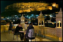 Travelers on rooftop terrace with view of Mehrangarh Fort by night. Jodhpur, Rajasthan, India (color)