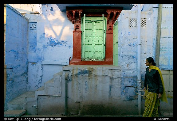 Woman walks infront of blue tinted whitewashed wall. Jodhpur, Rajasthan, India (color)