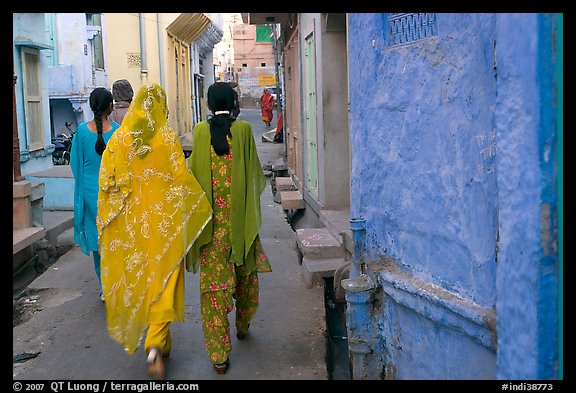 Women walking in narrow alley with blue walls. Jodhpur, Rajasthan, India