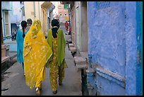 Women walking in narrow alley with blue walls. Jodhpur, Rajasthan, India (color)