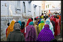 Women in colorful sari walking a  narrow street during wedding. Jodhpur, Rajasthan, India (color)