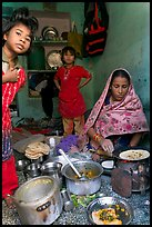 Woman cooking, flanked by two girls. Jodhpur, Rajasthan, India (color)