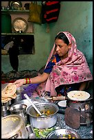 Woman with headscarf stacking chapati bread. Jodhpur, Rajasthan, India (color)