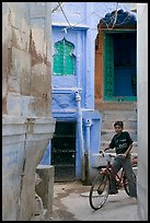 Boy riding a bicycle in a narrow old town street. Jodhpur, Rajasthan, India (color)