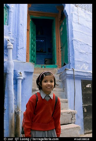 Schoolgirl standing in front of a house with blue tint. Jodhpur, Rajasthan, India (color)