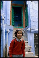Schoolgirl standing in front of a house with blue tint. Jodhpur, Rajasthan, India