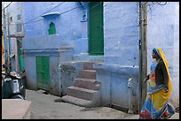 Woman walking in narrow street with blue walls. Jodhpur, Rajasthan, India (color)