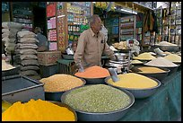 Man in front of grain and spice store, Sardar market. Jodhpur, Rajasthan, India ( color)