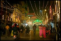 Women walking in street with illuminations. Varanasi, Uttar Pradesh, India (color)