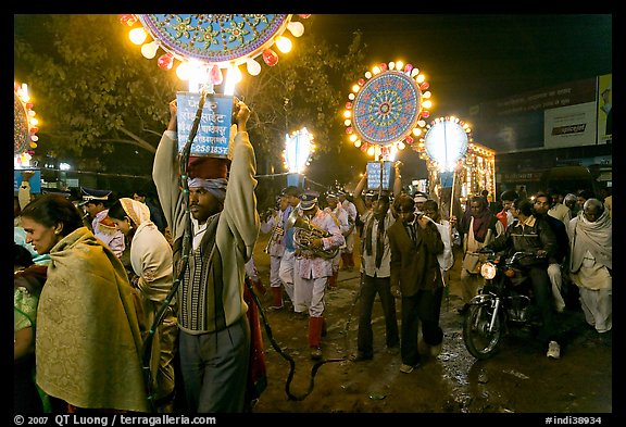 Men carrying bright electric signs during wedding procession. Varanasi, Uttar Pradesh, India (color)