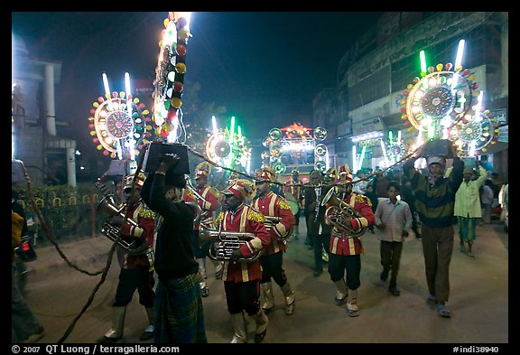 Musicians, men carrying lights, and carriage during wedding procession. Varanasi, Uttar Pradesh, India (color)