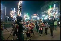 Musicians, men carrying lights, and carriage during wedding procession. Varanasi, Uttar Pradesh, India