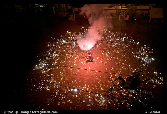 Man firing fireworks in middle of street ahead of wedding procession. Varanasi, Uttar Pradesh, India