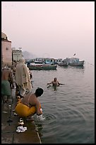 Hindu men dipping in the Ganges River at dawn. Varanasi, Uttar Pradesh, India