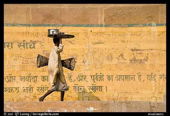 Man carrying a plater in front of wall with inscriptions in Hindi. Varanasi, Uttar Pradesh, India (color)