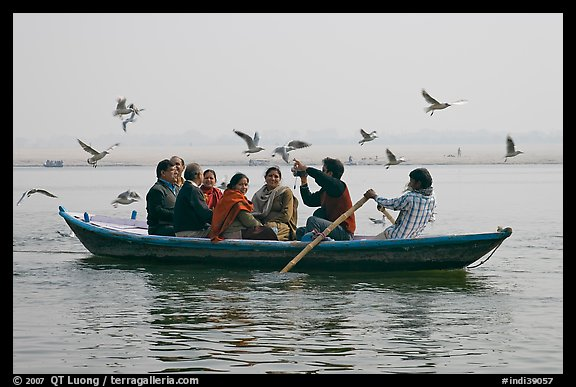 Indian tourists on rawboat surrounded by birds. Varanasi, Uttar Pradesh, India (color)