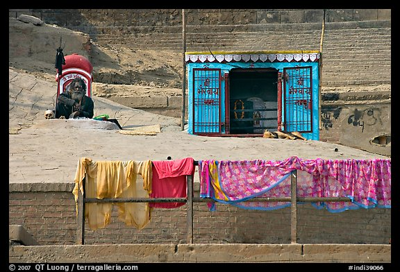 Sadhu sitting next to shrine and laundry. Varanasi, Uttar Pradesh, India (color)