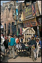 Man moving devotional image and children on rickshaw. Varanasi, Uttar Pradesh, India ( color)