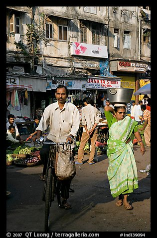Man riding bike and woman with basket on head, Colaba Market. Mumbai, Maharashtra, India (color)