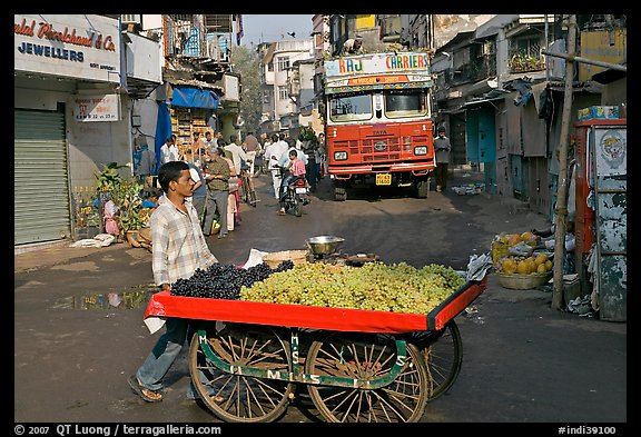 Vegetable vendor pushing cart with truck in background, Colaba Market. Mumbai, Maharashtra, India (color)