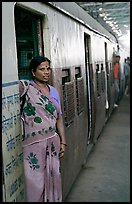 Woman standing at door of suburban train. Mumbai, Maharashtra, India