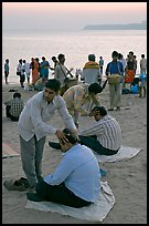 Head rub given by malish-wallah, Chowpatty Beach. Mumbai, Maharashtra, India (color)