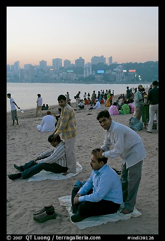 Head masseurs and Mumbai skyline at sunset,  Chowpatty Beach. Mumbai, Maharashtra, India (color)