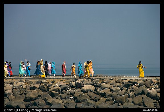 Women walking on  jetty in the distance, Elephanta Island. Mumbai, Maharashtra, India (color)